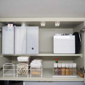 コンロ周りに置き地がちな調味料も、狭いキッチンだとかさ張ってしまいがちに。そんな時は、吊り戸棚に調味料をまとめて収納すると、すっきりと見栄えよく収まります。