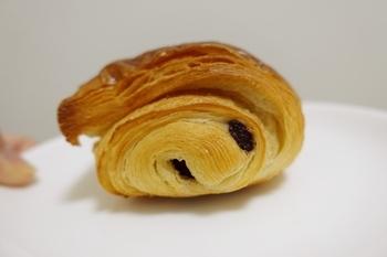 クロワッサン生地にシナモンときび糖を加えた『バトン・シュクレ』など、ヴィエノワズリーも若干あり。 甘にがいチョコレートとバターの風味が溶け合う『パン・オ・ショコラ』(画像)はオトナの味。