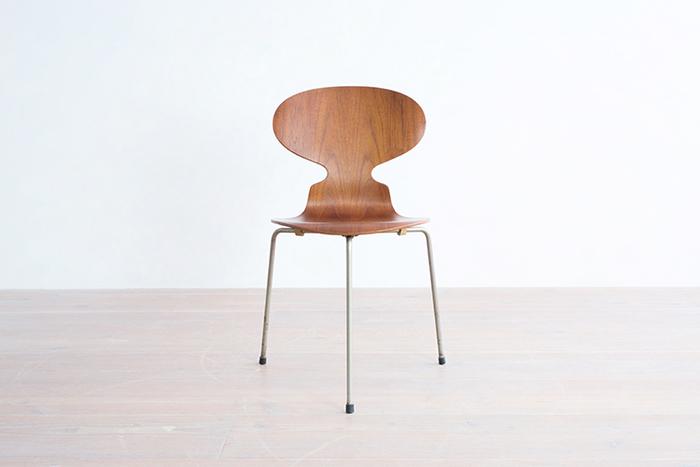 """一目でインパクトを与える「アントチェア」。個性的なのに落ち着きがあり、木製なのに疲れさせず。積み重ねても美しさをキープする完璧さ。デンマークの建築家アルネ・ヤコブセンが1952年にデザインを発表した当初、""""蟻""""の脚は、このように3本でした。現在は4本脚も制作されていますが、斬新さにこだわるならヴィンテージ・モデルを。"""