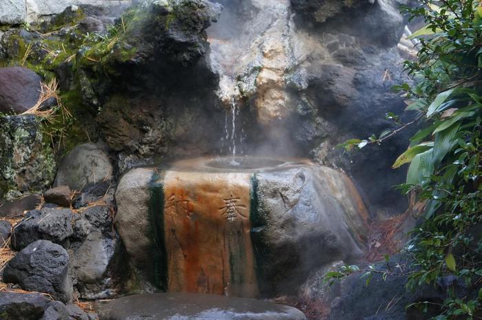 """日本有数の温泉郷である熱海は、源泉の数多く、古くから武将の湯治の場であり、江戸初期に家康公が湯治した以降熱海の湯は、徳川御用達の名湯として広く知られるようになり、江戸中期以後は、庶民の湯治場として栄えました。  【画像は、平安期から""""湯治の神""""として知られる「湯前神社(ゆぜんじんじゃ)」の手水舎。 湯前神社の境内には、三代鎌倉将軍・源実朝が詠んだ歌碑(『都より巽にあたり出湯あり 名はあづま路の熱海といふ』)があり、鳥居の脇にある手水舎では、熱海本来の源泉とされる「大湯」が今も湧いています。】"""