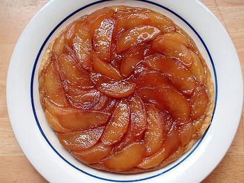 タルトタタンは、かつてフランスのホテル「タタン」で、経営者の女性がアップルパイに使うりんごを焦がしてしまい、仕方なくタルト生地をのせて焼き、ひっくり返してみると偶然にも絶品のお菓子ができ上っていたという説や、焦がしたりんごタルトを間違ってひっくり返してしまったという説も。それ以来、ホテルの看板スイーツになりました。