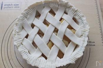 パイシートを細く切り、縦横に均等に並べたら、格子状に交互に通していきます。ふちをフォークの背などで押し付けて接着させ、上から溶き卵を表面に塗ります。