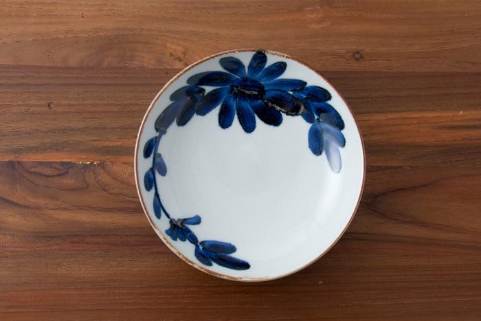 400年以上の歴史を持ち、庶民のための器として長く愛されている波佐見焼。こちらは有限会社マルヒロが展開する波佐見焼ブランド・BAR BARの「いろは」シリーズ、菊紋のお皿です。BAR BARは昨年まで「馬場商店」という名で展開されていました。  「いろは」シリーズのお皿は、職人さんが筆をもち、フリーハンドで絵をのせています。器を囲むように描かれた、シンプルながらも大胆な菊紋が特徴的。茶色の縁取りが、さらに引き締まった印象をつくり、自ずと中心に何かをのせたくなりますね。