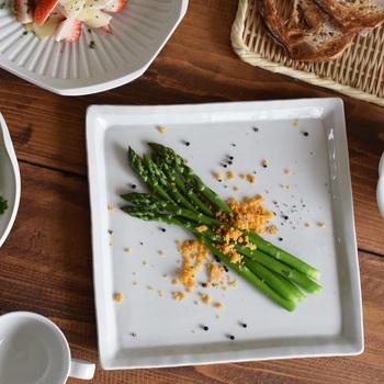 凛とした美しさの中に、素朴な温かさを感じる白磁の「角大皿」。磁器ならではのなめらかな質感と、どっしりとした重厚感のある佇まいも魅力です。リム(縁)が一段立ち上がった形状になっているので、お料理を盛り付けると、まるで絵画の額縁のように美しく引き立ててくれます。