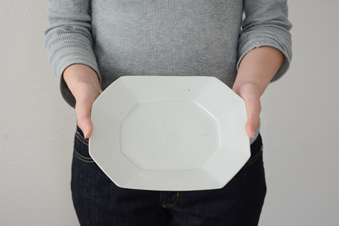 こちらは白磁のやわらかな風合いと、大き目のリムが特徴的な「八角長皿」です。うっすらと灰色を帯びた淡く優しい色調と、表面に黒い点がまだらに浮かび上がる素朴な仕上げも魅力。八角長皿のナチュラルな色は和食器にも洋食器にも合わせやすく、普段使いはもちろん、特別な日のおもてなしにもおすすめです。