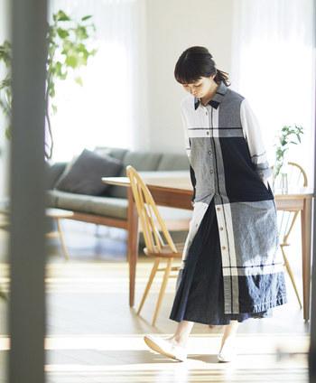 コットン100%の着やすい素材に、びっくりするくらい大きなチェック柄をのせたシャツワンピース。裾にはサイドに深くスリットが入っているので、インナーに穿いたスカートやパンツをチラチラ覗かせて、レイヤードを思いっきり楽しむのが正解。フロントオープンタイプなので、もちろん暖かい季節のコートとしても活躍しそうです。
