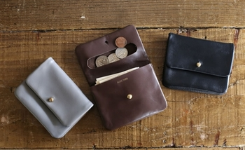 アリスパークの二つ折り財布は、無駄のないミニマルなデザインが特徴。1枚の牛革を折り曲げて縫い合わせたシンプルな構造となっていて、計算し尽くされたデザインは、まさに建築さんならではです。  真鍮の留め具を開けると、片方にはコインケース、もう片方には2つのポケットが付いています。1つのポケットには約10枚のカード類を収納できます。