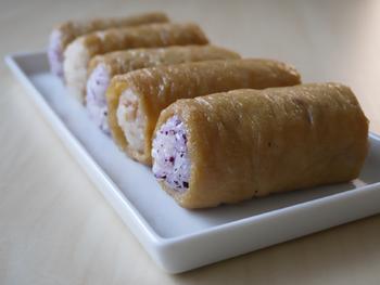 いなり寿司は油揚げに詰めるだけでなく、巻いてアレンジするのもおすすめです◎酢飯に鶏そぼろとゆかりを混ぜたごはんを甘く煮た油揚げでクルクルと巻いています。