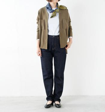 ジャケットと同系色のスカーフを、少し斜め向きにして結んでいる着こなしです。まっすぐに結ぶだけよりも、おしゃれ上級者感が増すスカーフの活用法ですね。