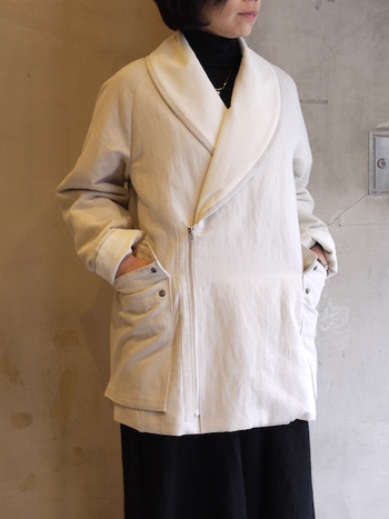 白のコートは、ウールではなくコットンなど軽い素材を選べば、カジュアルなスタイルに合わせやすくなります。こちらのコートは中綿が入っているのでとても暖か。装飾が目立たないデザインでありながら、大きめの襟やポケットがいいアクセントになっています。
