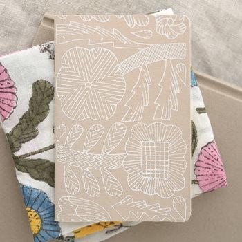 シンプルなノートには、素敵なカバーをつけて。ミナペルホネンの花の線画が描かれたノートカバー。ナチュラルカラーの控えめデザインなので持ち歩きにも◎
