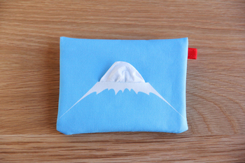 """富士山の7合目付近まで描かれた「ティッシュケース」は、ティッシュを引き出すことで""""富士山""""が完成。後ろにはファスナーがついたポケットもあるので、絆創膏なども入れられるので便利です!"""