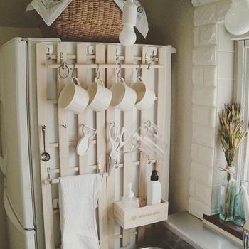 冷蔵庫横のデッドスペースを有効活用できるDIYアイデア。すのこにハテナフックやロープフックを取り付けて、ピーラーや計量カップなどのキッチンツールを吊るして収納しています。すのこはマグネットで固定するので、賃貸でも安心!木の風合いでナチュラルで優しい印象です♪