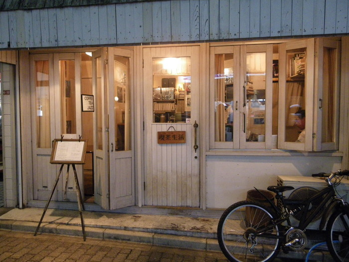 東京メトロ丸ノ内線 東高円寺駅すぐそばにある、ニコニコロード商店街にたたずむ「喫茶生活」。ジャズ初心者の方でも入りやすいホワイトカラーのウッディーな外観が目印です。