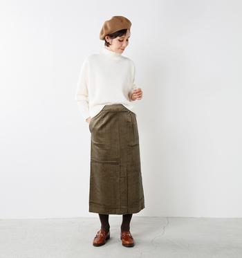 白のニットを、カーキのタイトスカートに前だけインしたスタイルです。前の部分をちょこっとだけ入れるのがポイントで、きっちりし過ぎないことでナチュラルな着こなしが完成します。
