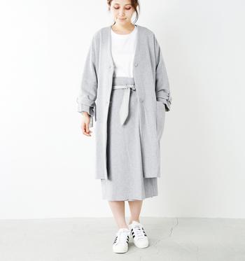 グレーのタイトスカートに、同色のライトアウターを羽織ったスタイル。インのトップスはホワイトを選んで、全体のトーンを揃えたバランスのいい着こなしに仕上げています。