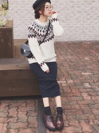 ノルディック柄の白ニットに、ネイビーのタイトスカートを合わせた着こなし。長さの無いトップスをアウトスタイルで着用する場合は、丈が長すぎないタイトスカートを合わせるのがポイントです。