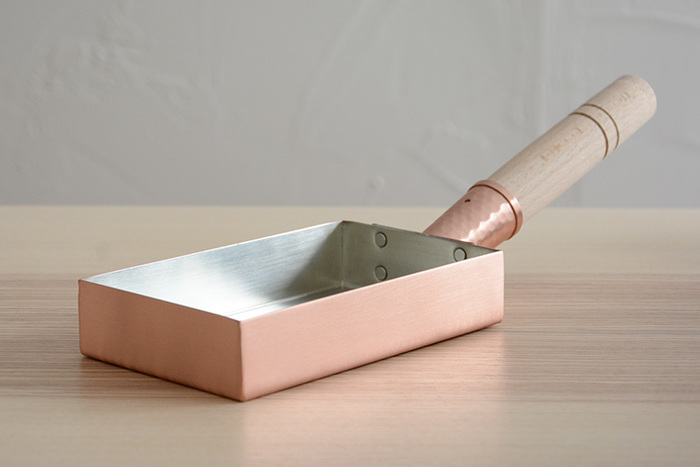 大正11年創業の「工房アイザワ」。日本が誇る金属加工産業の集積地、新潟県燕市で、銅やステンレスなどを使ったキッチン用品を展開している老舗の人気ブランドの「純銅製玉子焼き器」。W150mm × D90mmの関西型の純銅製なので、だし巻き卵を作るのに最適。板厚も1.2mmあるので、保温性も熱の伝導率も良く、ふんわりとしただし巻き卵が作れそう。