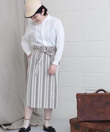 トップス次第でさまざまなルックがつくれる、エプロン風デザインのスカート。丸衿のシャツを合わせれば、品行方正な上品スタイルが完成します。