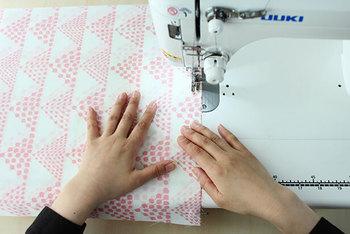 表布となる生地2枚を中表(生地の表が内側になるように合わせる。柄の向きに注意)にして、縫い代を1cm取って、ミシンで直線縫いします。