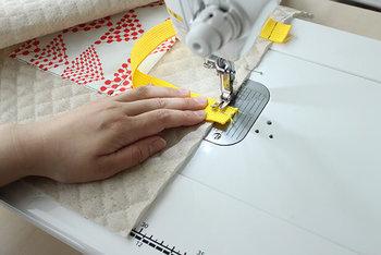 持ち手を付けます。きちんとバッグの中央にバランスよく持ち手が来るように、定規を使って印をつけて、ミシンで縫い付けます。