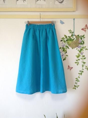 パキッとしたターコイズブルーが素敵なスカート。あえて雨の日に着て、街に色をプラスしてあげるのも素敵です。