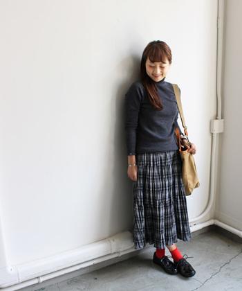 定番のトラッドルックも、シワ感のあるスカートなら人とは違う装いに。ソックスの鮮やかなレッドが効いています。