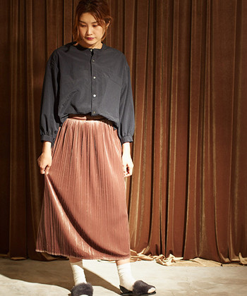 光を美しく反射するベロアのプリーツスカート。プレーンなブラックのブラウスで、その華やかさを存分に引き立てます。