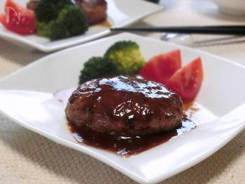 粘りが出るまでよくこねた肉ダネに、玉ねぎと他の材料を加えて小判型にまとめます。玉ねぎは、生のままでOK。シャキシャキと食感もよく、ジューシーなおいしさをより引き立ててくれるのだとか。あとは、中央をくぼませたハンバーグを、じっくりと両面焼いていきます。