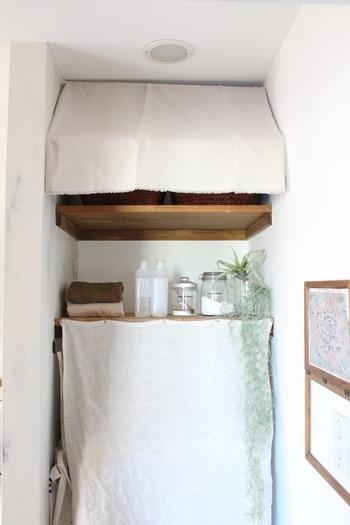 洗濯機置き場の生活感をできるだけなくすために、見せたくないところは布でうまく目隠し。突っ張り棒を2本使って、オーニング風に布を垂らしたところがおしゃれ。奥行を感じるので、窮屈な感じもなくていいですね。