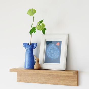 飾り棚にリサ・ラーソンの花瓶に合わせたブルーの絵をコーディネート。アイテムを2~3つに絞ると空間にゆとりができ、すっきりと見せることができます。