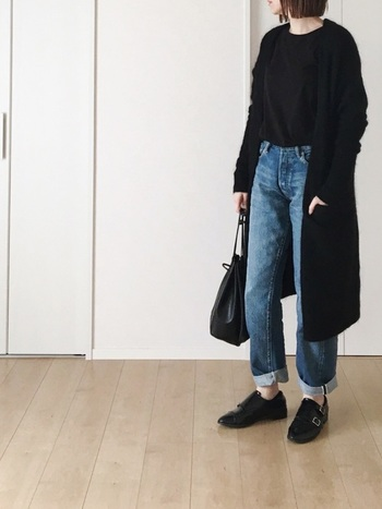 カジュアルな装いを上品に導いてくれる、やわらかなレザーの巾着。ボトム以外を黒でまとめるのもポイント。