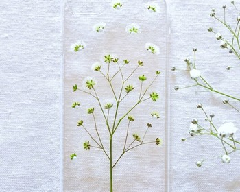 華やかなデザインが人気の押し花ケースは、かすみ草一種だけで大人っぽく。本物の押し花を使用しているため経年変化も楽しめるのだとか♪