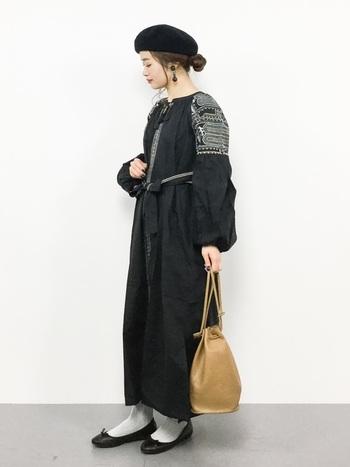 存在感のあるオリエンタルなブラックワンピースには、ベージュの巾着で抜け感を。ブラック×ベージュ×ホワイトで上品にまとめられています。