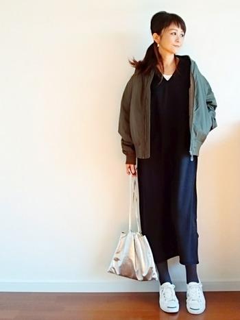 シンプルなワンピースとメタリックシルバーの巾着で、キレイめの大人カジュアル。重くなりすぎないよう、チラっと見えるグレーやホワイトの配分も参考になるスタイリングです。