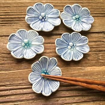シンプルにまとめたテーブルも、たったひとつ花の箸置きを置くことで、さりげなく華やかな印象に。小物で遊ぶのも、大人のたしなみのひとつですね。こちらは、ブローチのようにひとつずつ彫りを入れた、陶器の箸置きです。