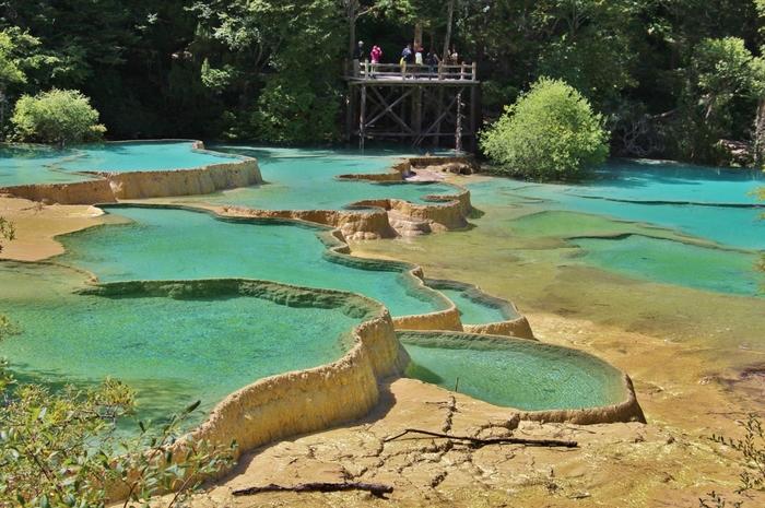 抜群の透明度を誇る黄龍の水は、陽射しや時間帯のよって刻々と色を変えていきます。棚田状の石灰岩に溜まった透き通る水、風によって形を変える水面の波、季節によって変わりゆく樹々の色……。ここでは、二度と同じ景色を見ることはできません。