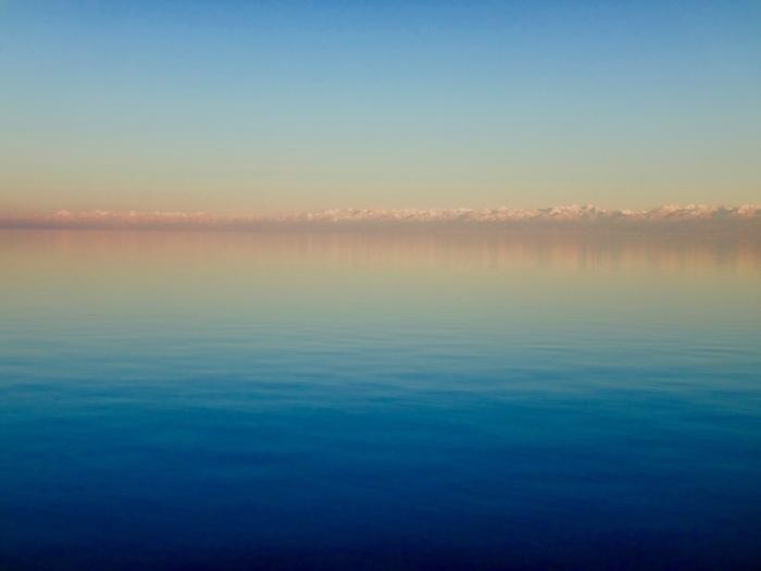 国土の約4割が標高3000メートルを超える高原の内陸国、キルギスの北西部に位置するイシククル湖は、琵琶湖の約9倍もの面積を持つ湖です。イクシシル湖は中央アジアを代表する古代湖で、玄奘三蔵の大唐西域記にもその存在が記述されています。抜群の透明度、陽射しを浴びて碧く輝く湖面、湖対岸に見える夏でも冠雪した険しい山岳地帯が見事に調和した抜群の景観美を持つイシククル湖は、「中央アジアの真珠」「キルギスの海」とも呼ばれています。