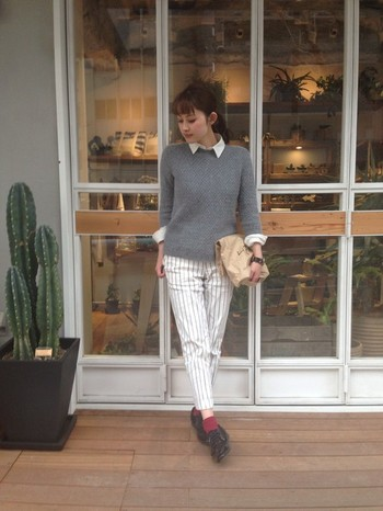 グレーのセーターから白シャツの襟を見せ、腕はさりげなくロールアップ、裾は出さずに上品に着こなしたスタイルです。