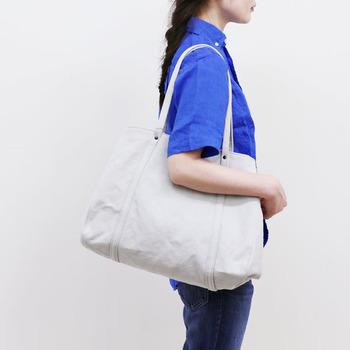 東京中目黒でデザイナー自らもミシンを踏み、帆布をはじめとしたオリジナルバッグを生み出している「ateliers PENELOPE」。  こちらは、台形のフォルムと細い持ち手が女性らしくてスマートな印象を与えるトートバッグ。もちろん、ノーマルな四角い形でも使えるようになっていて、荷物の量やスタイルに合わせること可能!雨にも強い特殊加工のおかげで、ヴィンテージのようなシワと風合いを楽しめ、持つだけでこなれ感のある着こなしを楽しめます。