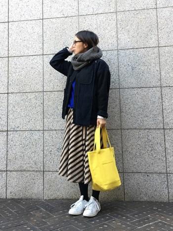 シックな冬のスカートコーデに、明るいタンポポ色のキャンバスバッグで春らしさをプラスして。足もとの白スニーカーと共に全体のトーンを軽やかにアップしています。