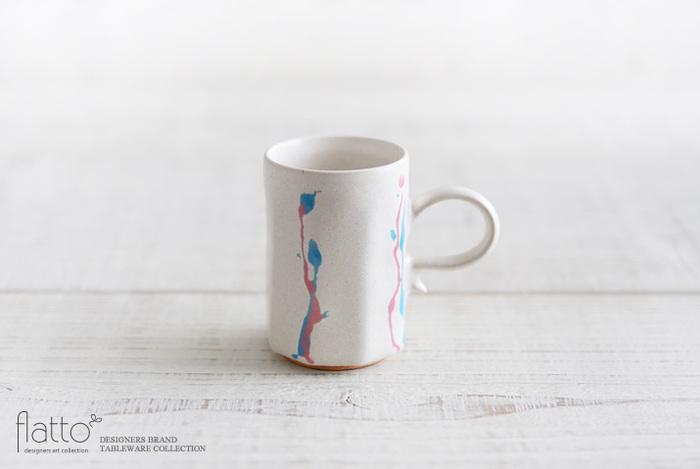 陶器の街「信楽」の出身である安田宏定さんのモダンなデミタスカップ。白の釉薬をベースに、筆で描かれた勢いを感じる桃色と青色の雫模様。カップの高台部分には銀彩が使われています。
