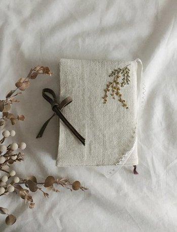 優しい風合いのリネン地に、手刺繍でミモザをあしらって。シルクのレースは栞としても使えます。 毎日の読書タイムにそっと寄り添ってくれるナチュラルなブックカバーに。