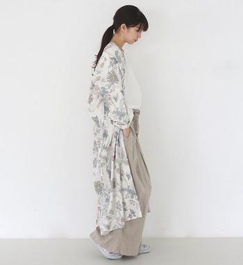 ベージュのワイドパンツに白トップスを合わせたシンプルコーデに、花柄のロングガウンを羽織ったスタイル。デザイン性のあるライトアウターは、一枚羽織るだけで華やかに見せてくれるので、休日コーデの強い味方です。