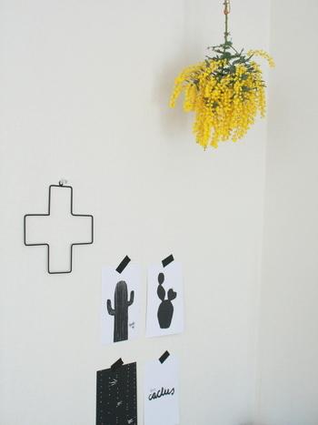 お花のボリュームを調えて、革紐で天井から吊り下げるというワザ。まるで照明のシェードのよう。