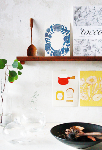 キッチンやリビングの壁に飾り棚を取り付けて。そこにちょこっとポストカードを置くだけでも雰囲気がずいぶん変わりますよ。