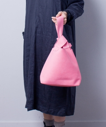 さくらピンクに染められた、ユニークな形のハンドバッグ。洋服はダークカラーにして、その鮮やかさを存分に楽しみましょう♪