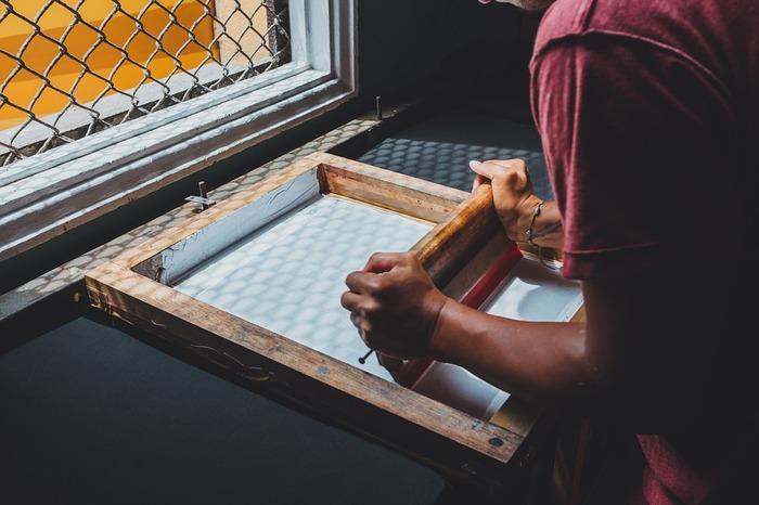 シルクスクリーンとは、版画技法のひとつです。メッシュ地の布に、インクが通る部分と通らない部分をつくり、それを版として印刷します。一度版を作ると、インクの色を変えて同じ柄を何度も印刷することができます。