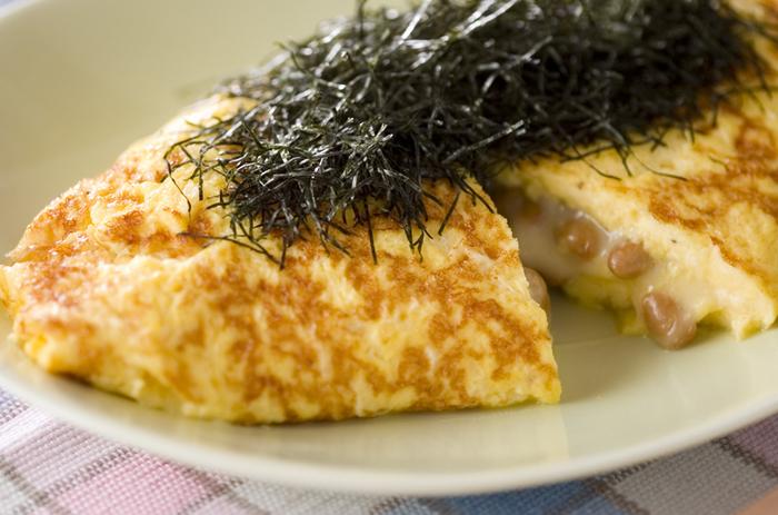 【納豆オムレツ】  納豆好きには定番の納豆オムレツ。おろしニンニクやチーズも入れてメインおかずになるような1品に仕上がっています。キレイな黄色のオムレツにお箸を入れると、とろりとした納豆とチーズがたっぷり。