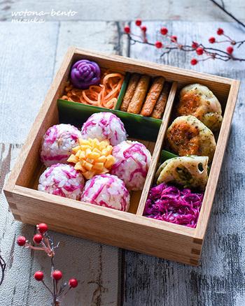 花びらは紅色の菊花のおにぎり、めしべは薄焼き卵の華やかな梅の花が咲くお弁当は、春のピクニックのお供にぴったり。紫芋で作るモチモチの薔薇団子も添えられていて、お花が満開です。